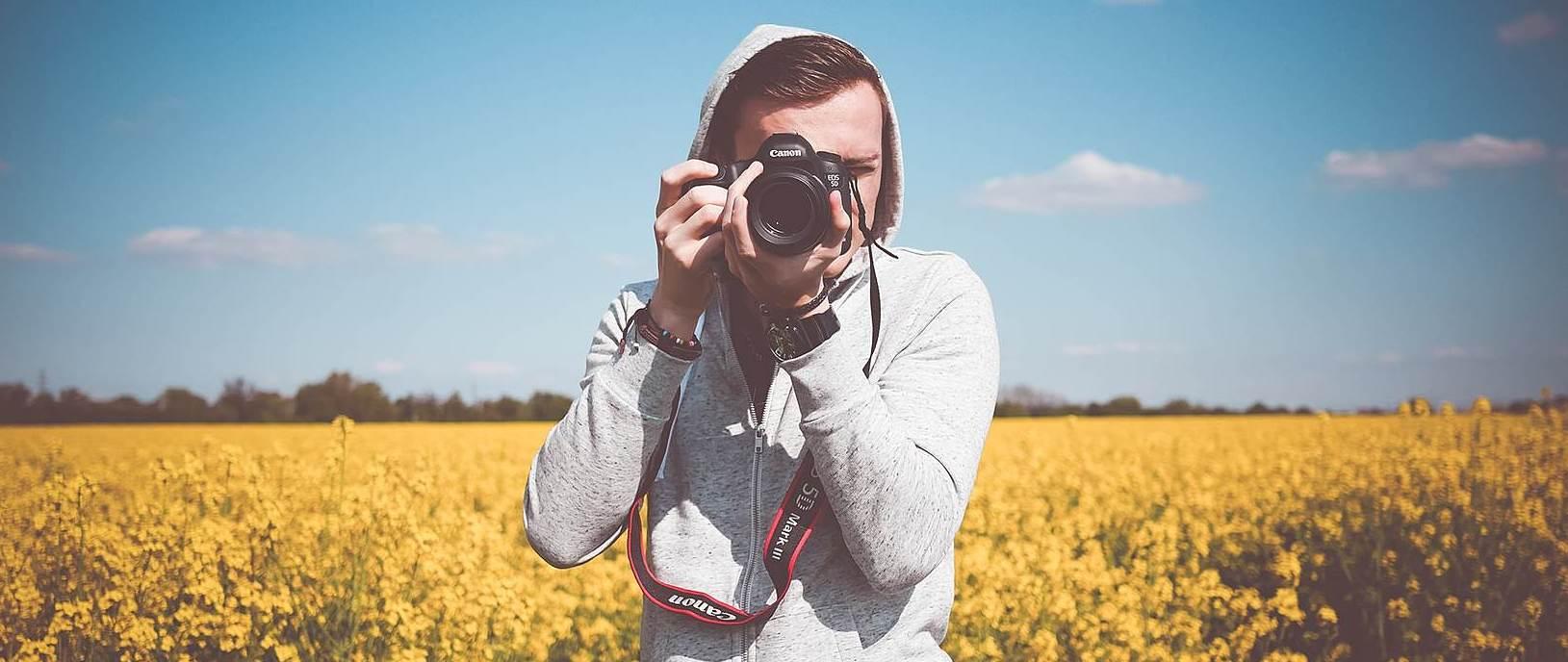 menino com câmera na mão apontando para você