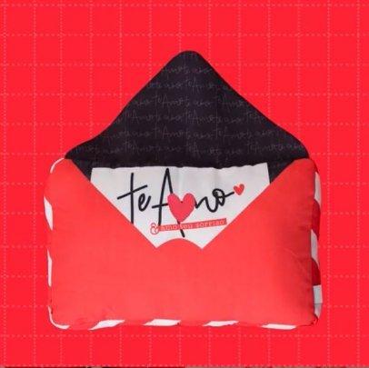"""Almofada vermelha em formato de envelope com estampa que simboliza uma carta, com a frase """"te amo""""."""