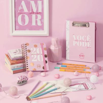 Agenda e planner personalizados em uma mesa rosa, com objetos de papelaria em volta.