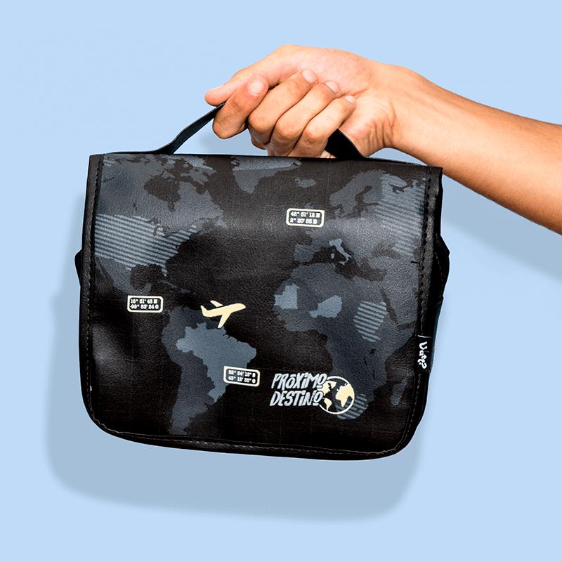 Uma mão aparece no canto direito segurando uma maleta estilizada com desenhos do mapa múndi e aviões.