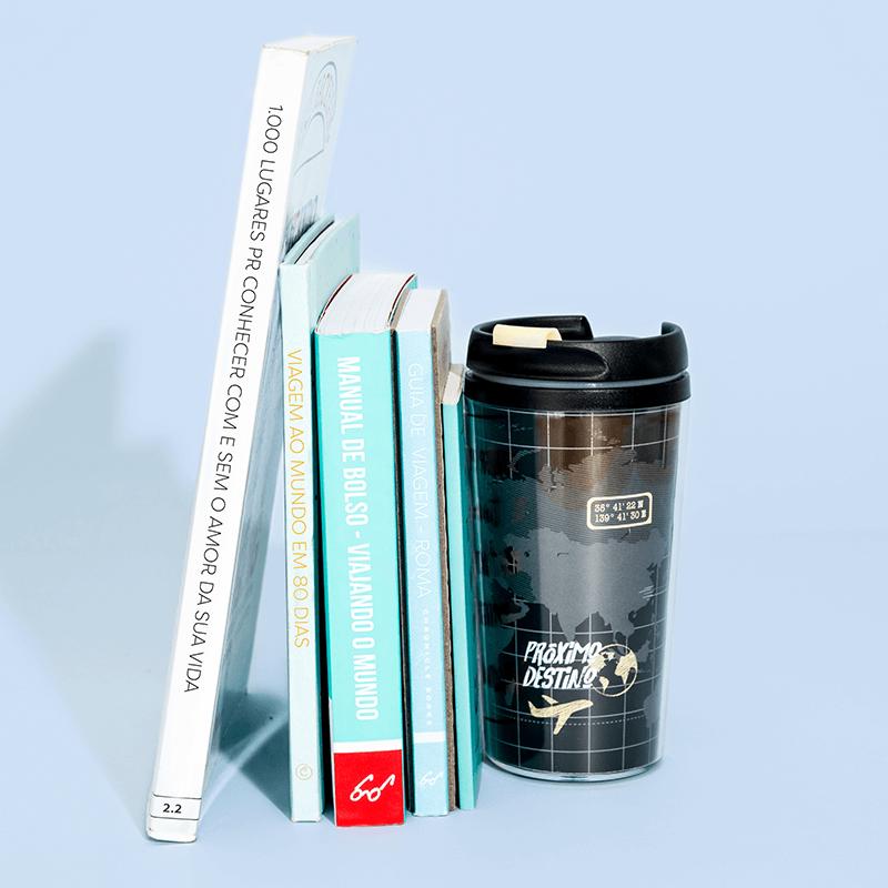 Livros sobre viagem e copo térmico estilizado com desenhos de mapa múndi e aviões.