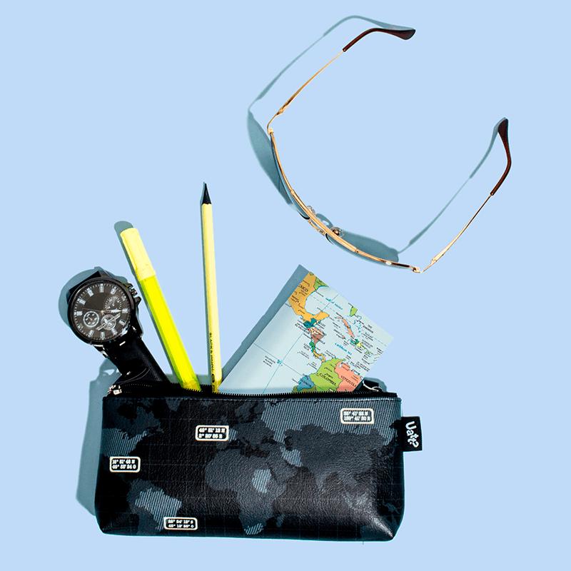 Fundo azul com um óculos e uma necessaire entreaberta, com um bloco de notas, um relógio e canetas.