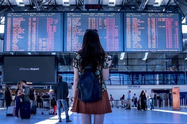 Moça vista de costas em frente a um painel de informações de voo num aeroporto.