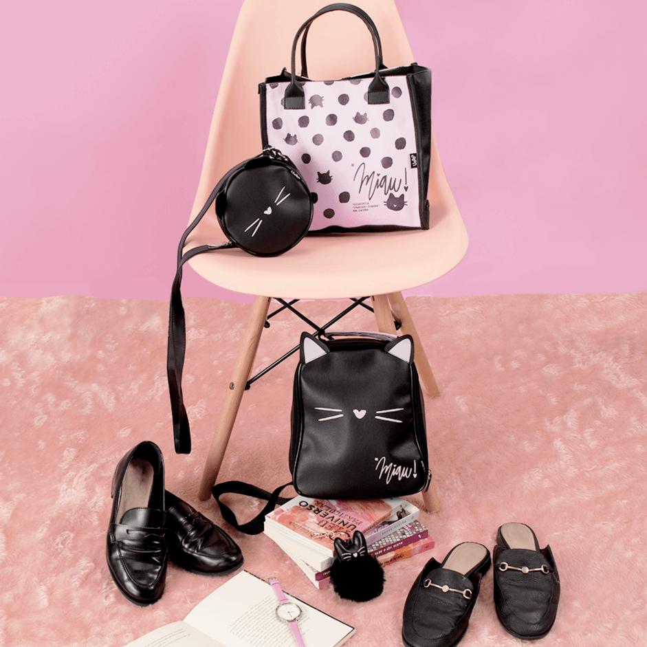 Imagem com fundo rosa, tapete rosa, dois pares de sapatos pretos no chão. Uma cadeira no centro abriga duas bolsas e no pé da caneira tem uma mochila posicionada em cima de alguns livros.