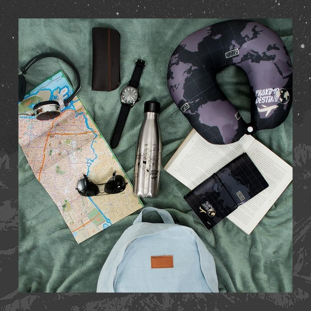 fundo verde com almofada de pescoço, mochila, mapa, óculos de sol, garrafa térmica e caderno de anotações