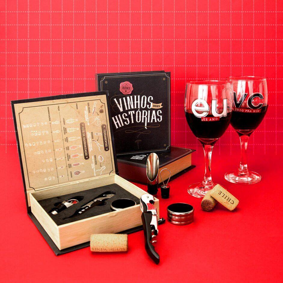 Imagem com fundo vermelho, caixa com acessórios para vinho e duas taças.