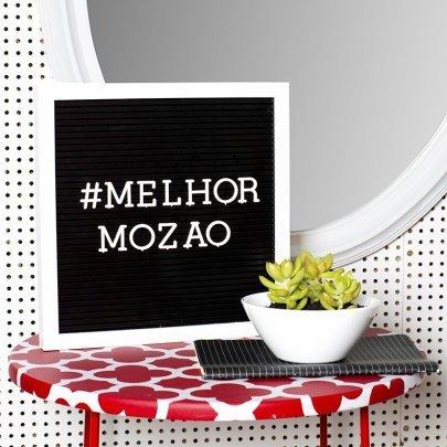 Imagem com quadro, caderno e planta em cima de uma mesa estampada. No fundo da imagem tem uma parede cm furinhos e um espelho redondo.