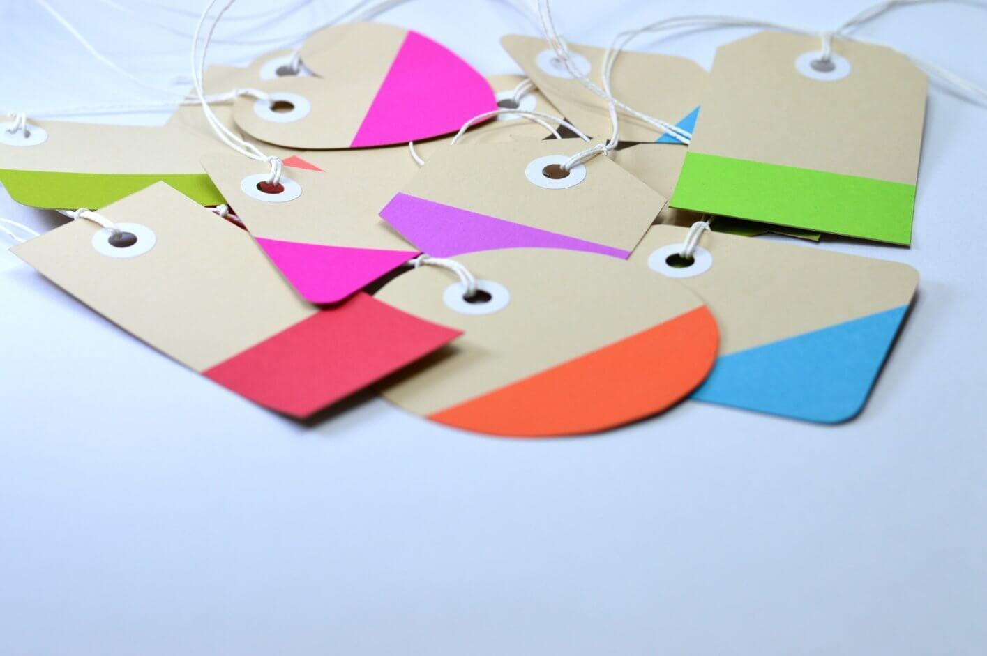 tags coloridas em rosa, laranja e azul.