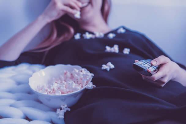 Imagem com uma menina deitada na cama com um pote de pipoca ao seu lado. Ela está comendo pipoca e tem algumas caídas em cima dela.