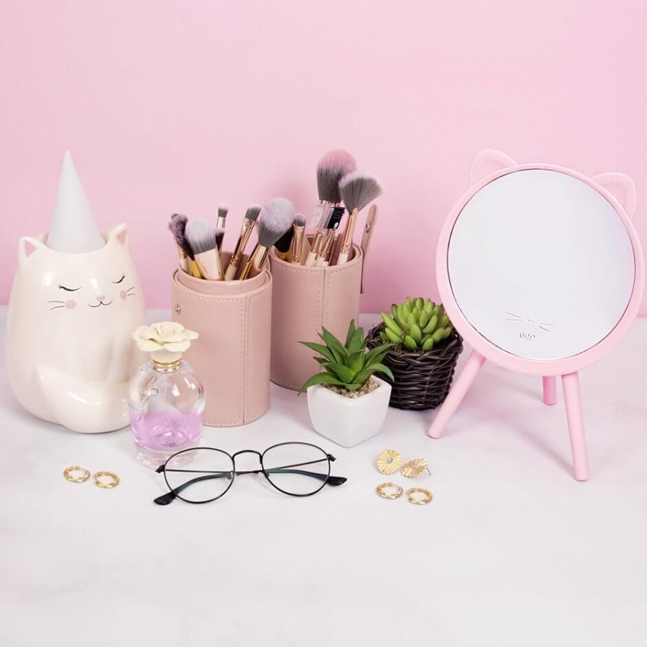 uma mesa com luminária de gato, porta pincéis de maquiagem, duas suculentas, um perfume e um óculos.