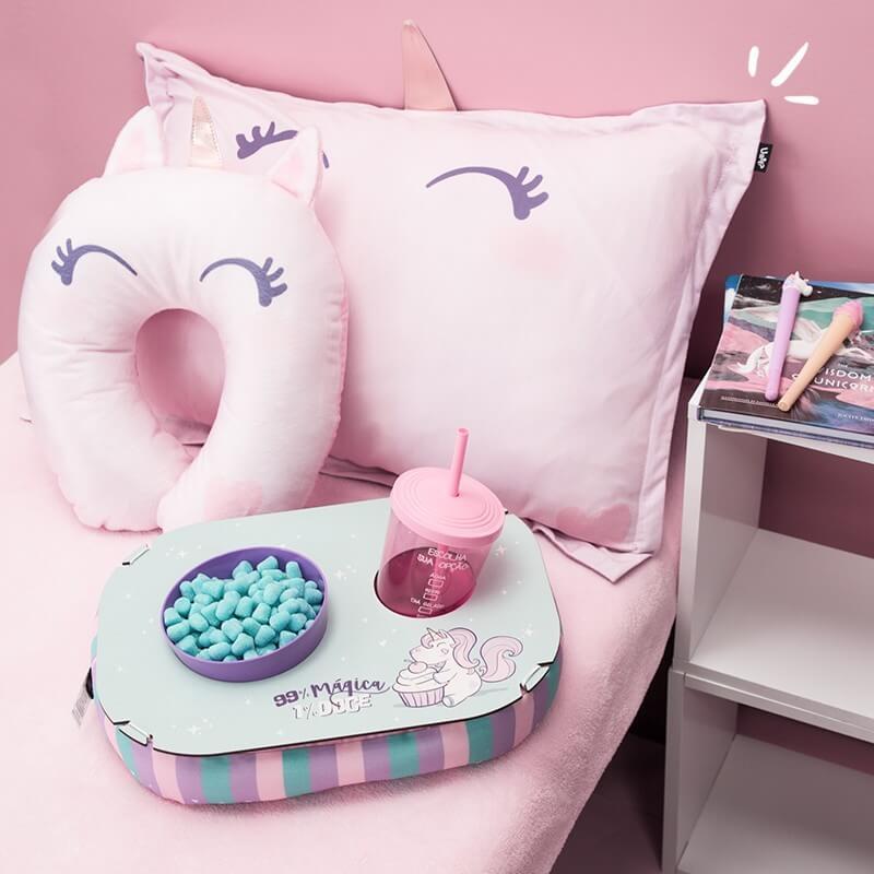 cama cor de rosa com travesseiro, almofada de pescoço e almofada de pipoca.