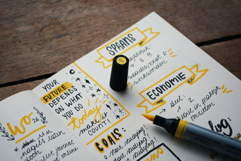 planner com anotações sobre economia e metas e um marca texto amarelo.