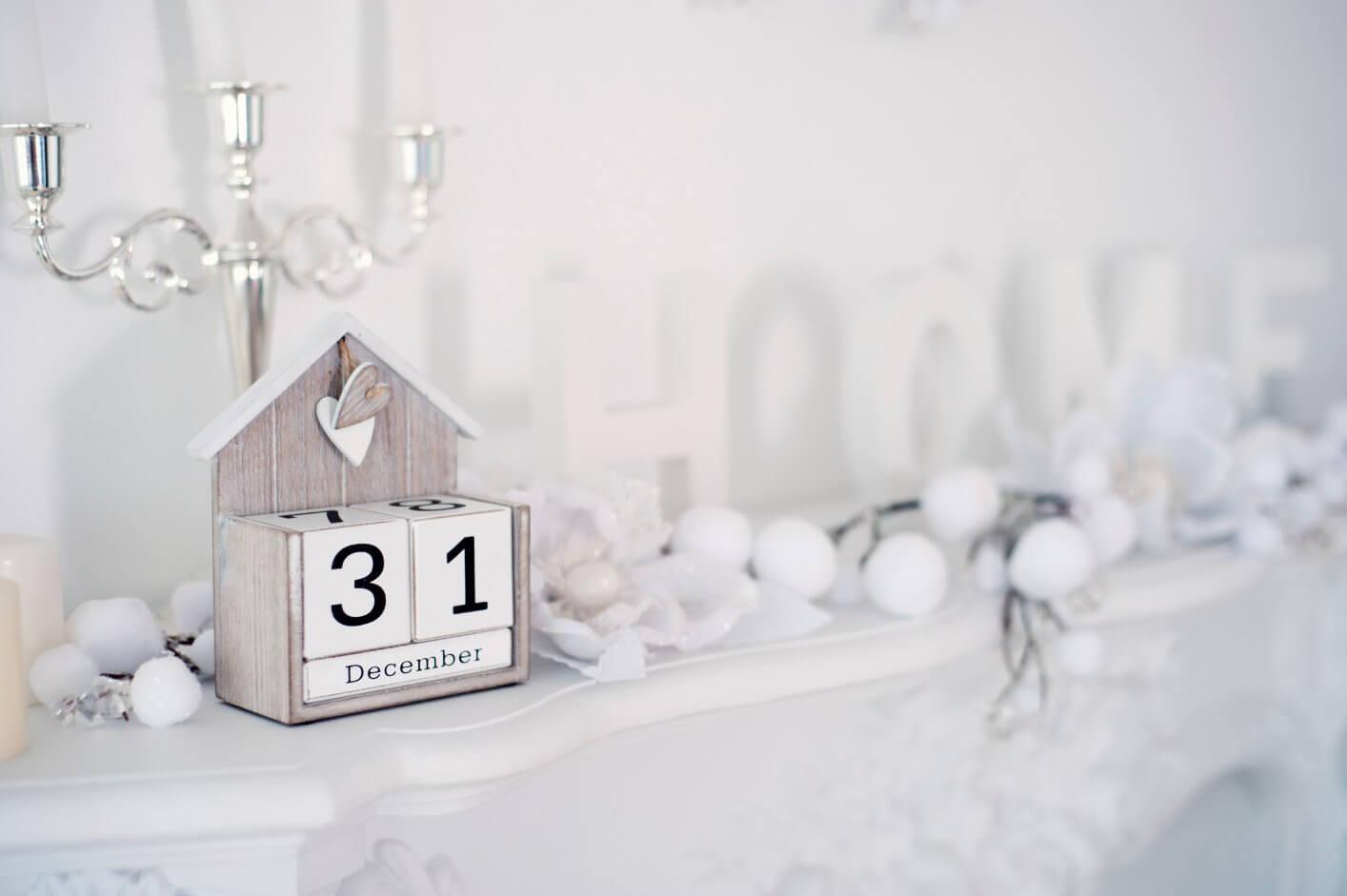 calendário de mesa de mdf em formato de casa com castiçal de prata ao fundo.