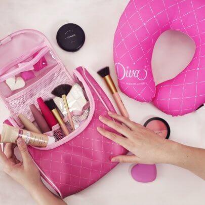 necessaire rosa com pincéis de maquiagem ao lado de uma almofada de pescoço rosa.