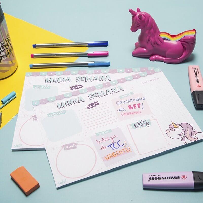 mesa com um planner semanal, dois marca textos, uma borracha e um unicórnio rosa.