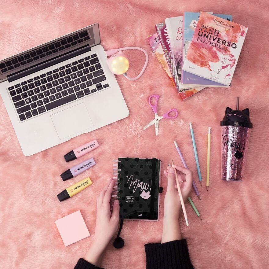 fundo rosa com notebook, livros, lápis de grafite, agenda, copo com canudo e marca-textos.