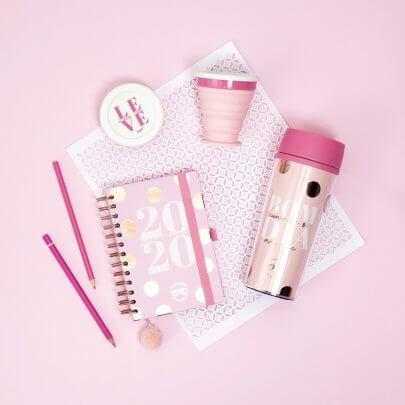 fundo rosa com um planner de 2020, dois lápis, um copo retrátil e uma squeeze térmica