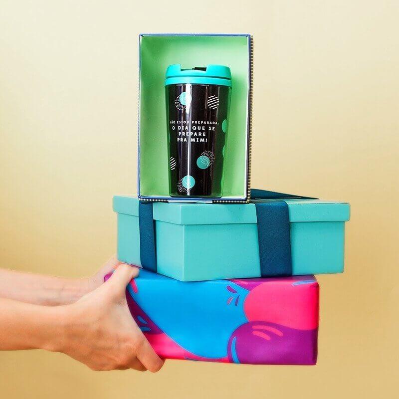 Imagem com mãos segurando duas caixas e um copo térmico dentro de uma delas.
