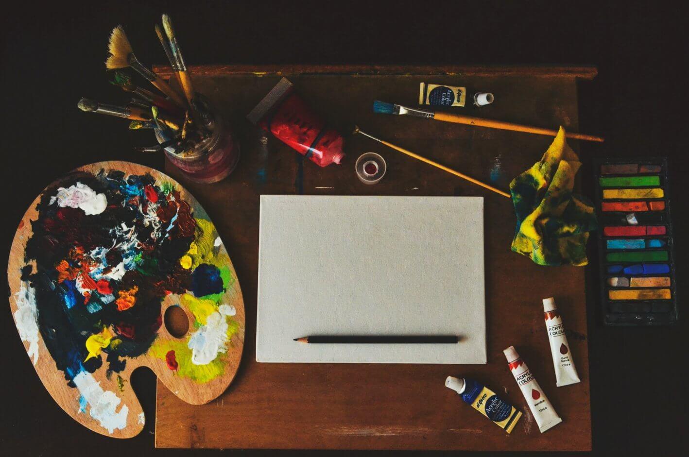 mesa com materiais de pintura: pincéis, bisnagas de tinta e um aparador para aquarela.