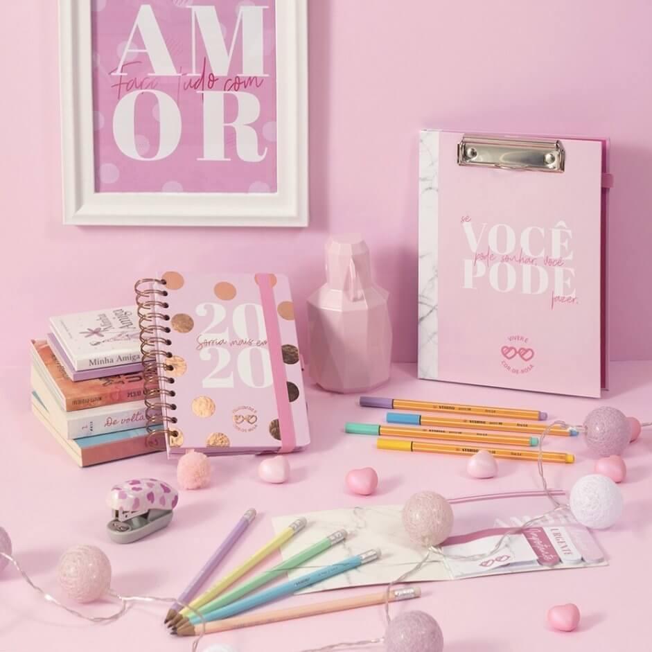 Mesa rosa com cinco lápis, cinco canetas, um planner e uma prancheta. O fundo é rosa.