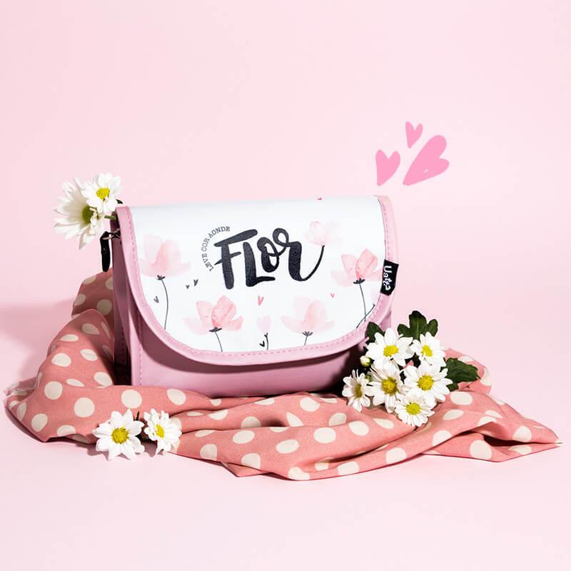 Imagem com fundo rosa e uma bolsa rosa.