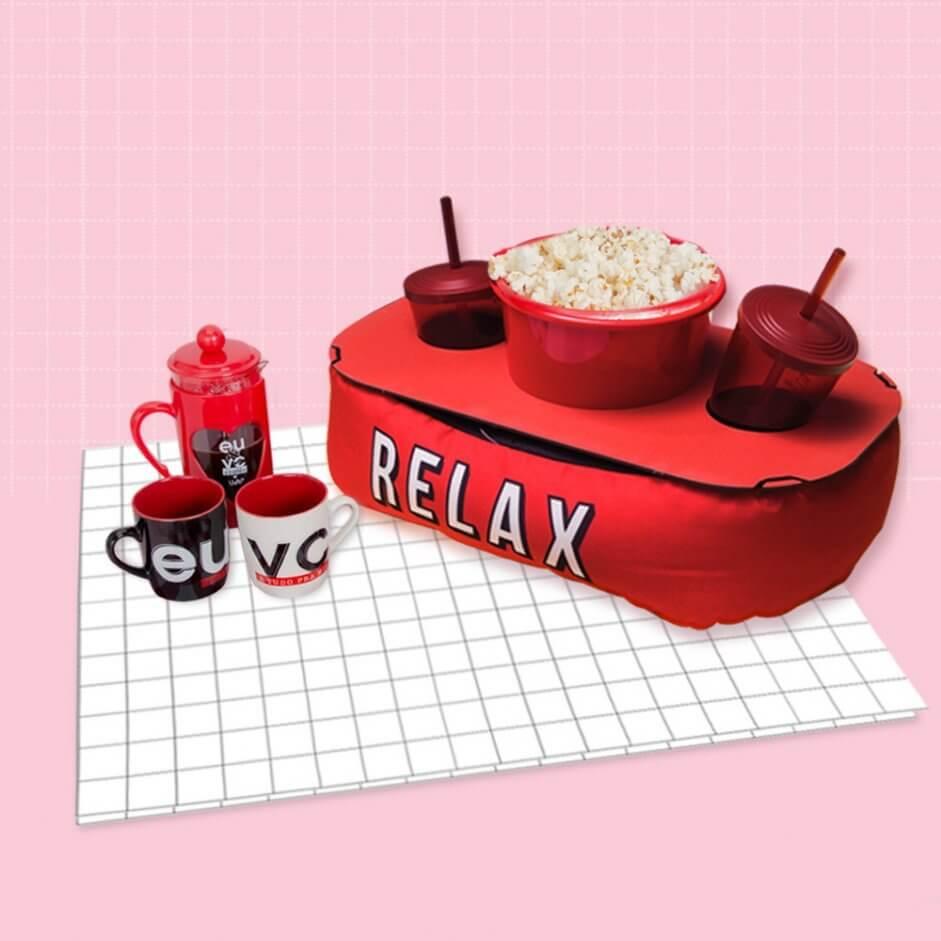 Imagem com fundo rosa, uma almofada para pipoca, duas canecas e uma jarra.