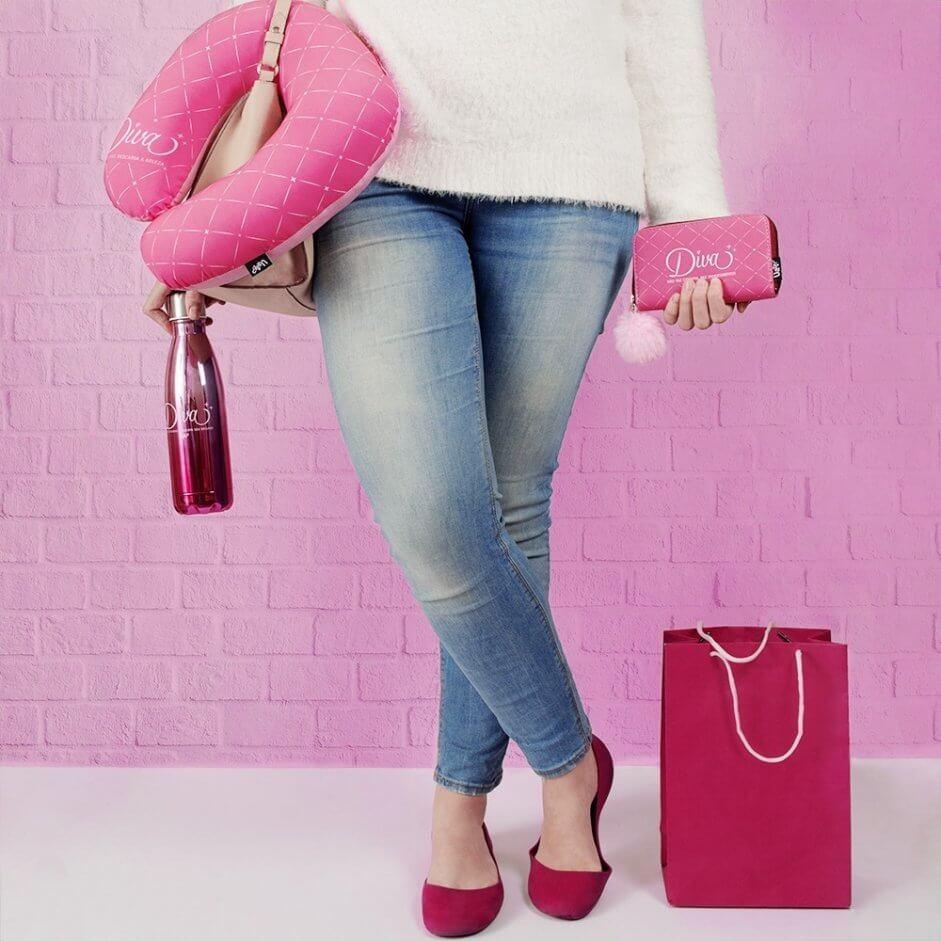 mulher segurando uma carteira rosa na mão esquerda, e na direita uma bolsa, uma almofada de pescoço e uma squeeze térmica. No chão tem uma sacola rosa de compras.