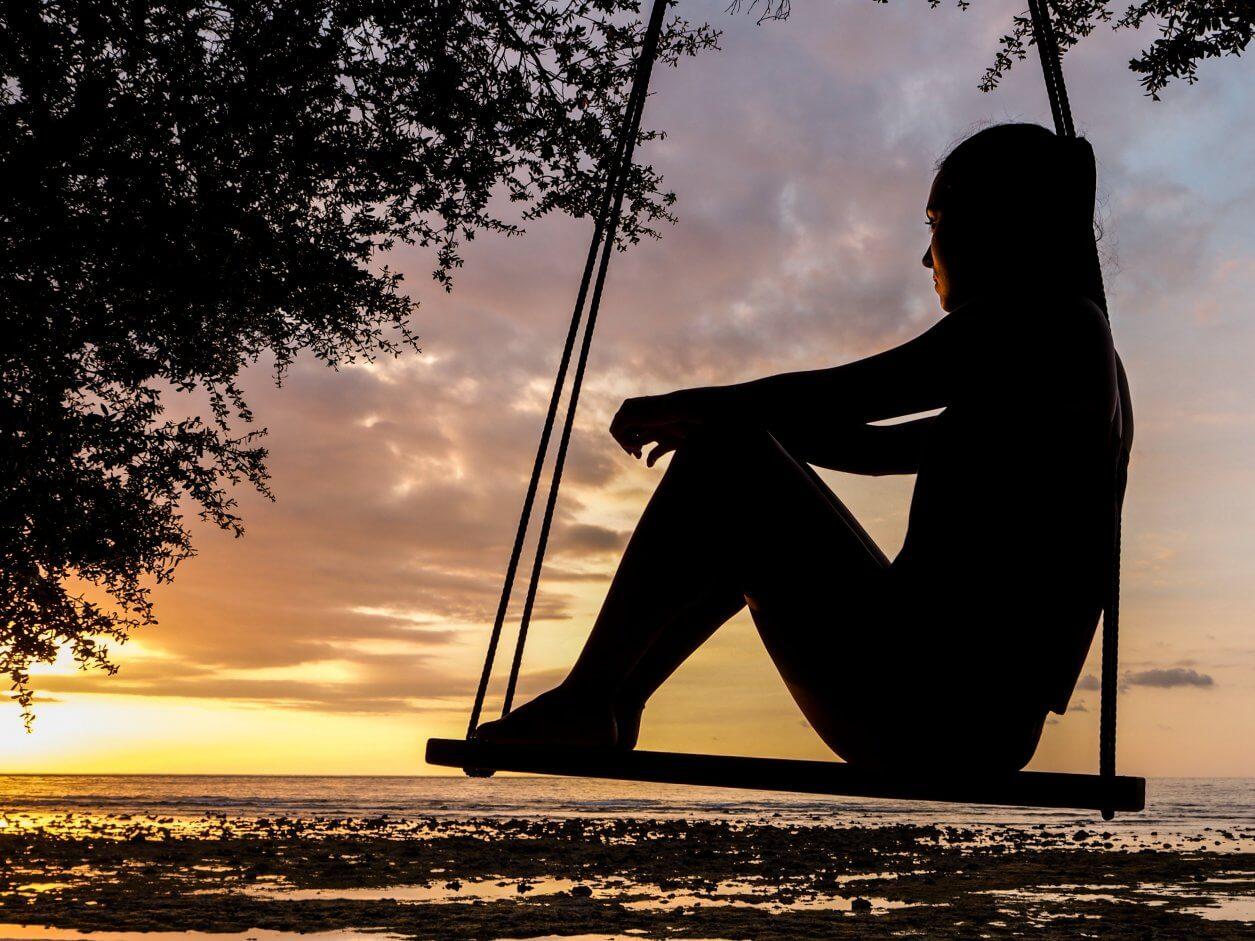 silhueta de uma mulher sentada em um balanço admirando o nascer do sol.