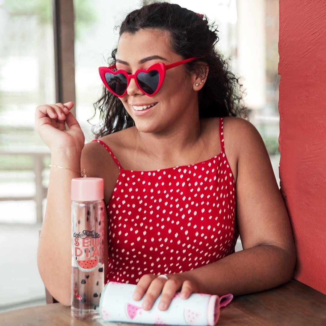 mulher de vermelho com um óculos de coração e uma garrafa de água.