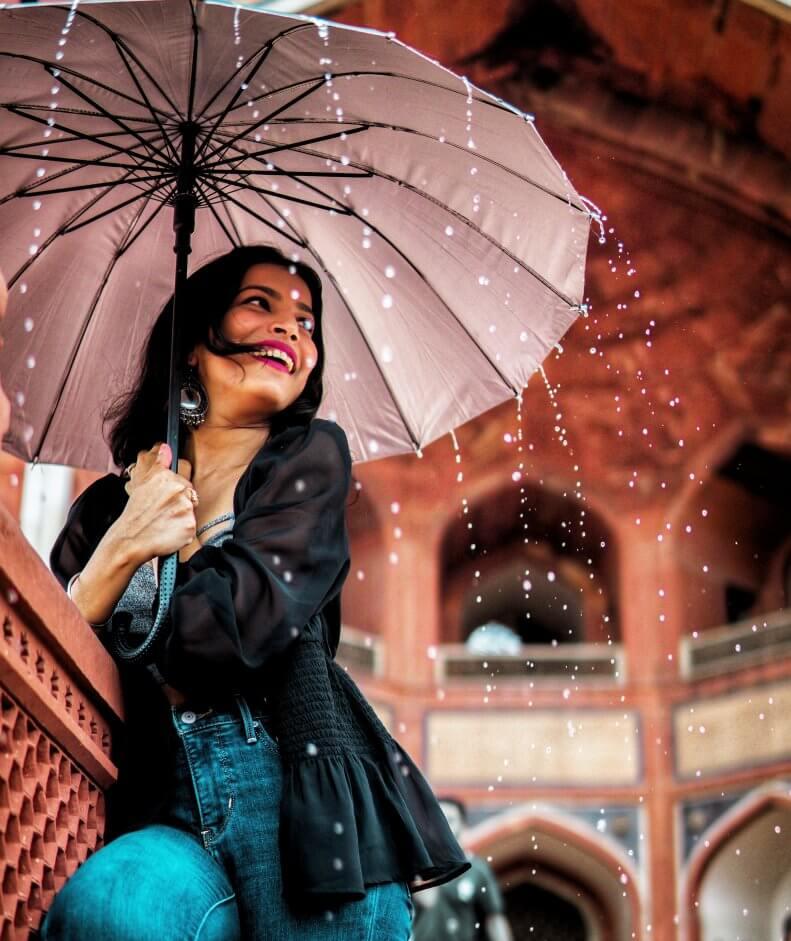 Mulher com guarda-chuva sorrindo.