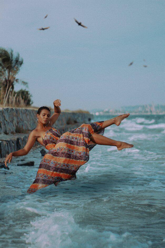 mulher pulando no mar com um vestido marrom e laranja.