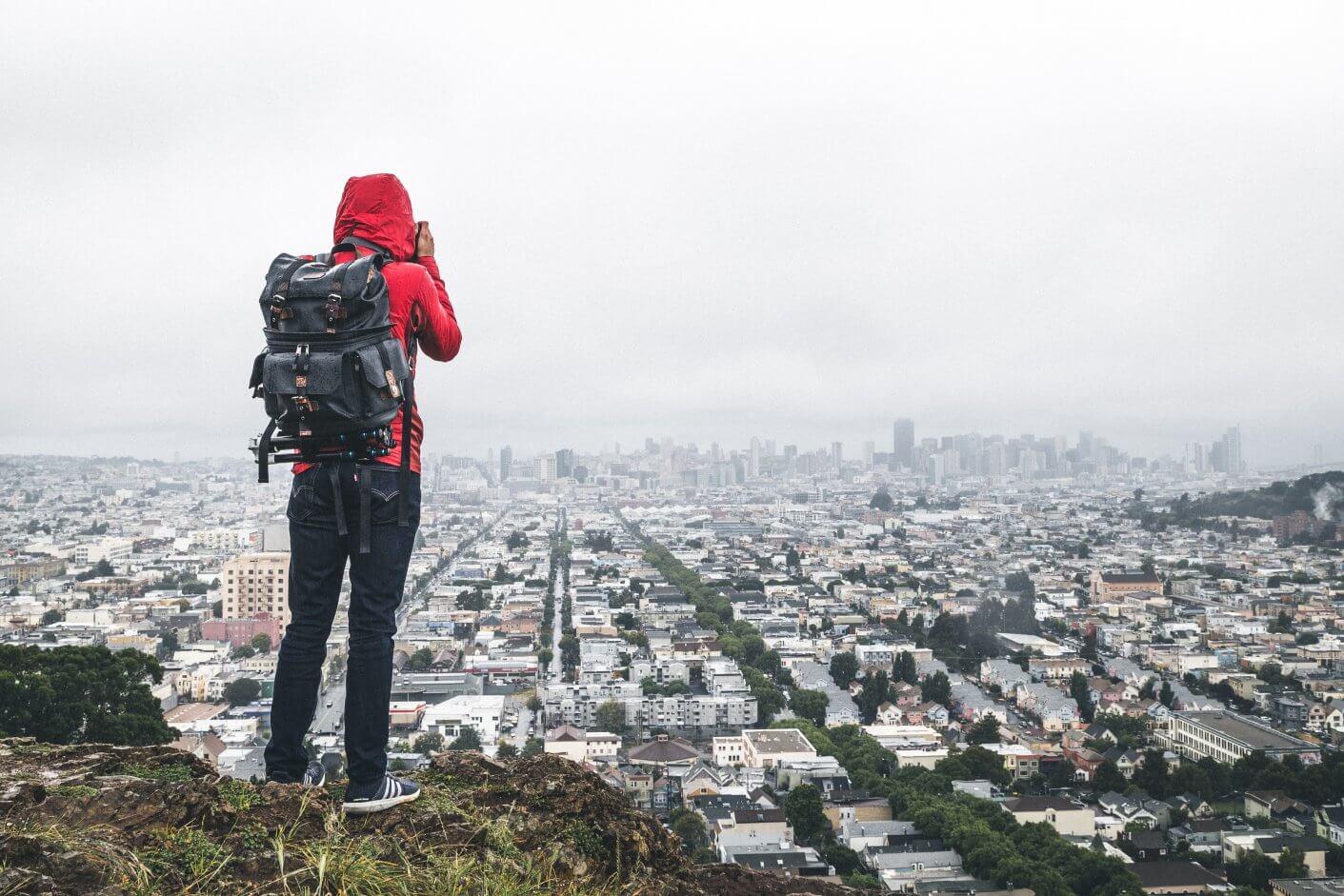 pessoa parada em um mirante natural para uma cidade cheia de casas e prédios baixos.
