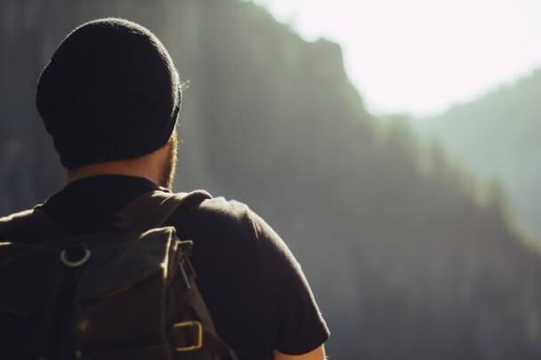 Homem de touca e mochila em uma trilha