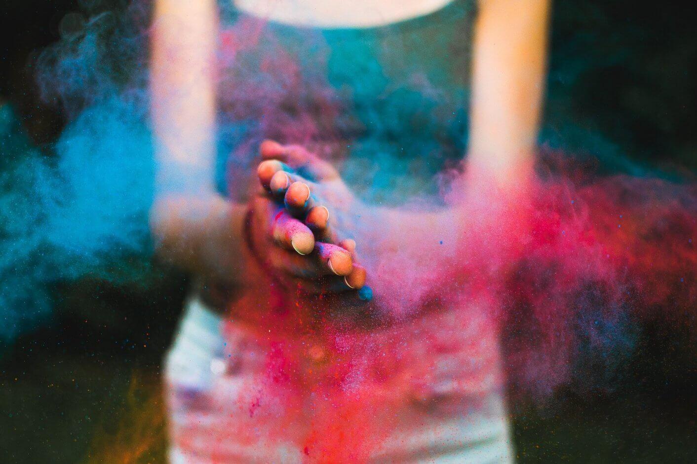 menina batendo as mãos com pó clorido azul e rosa.